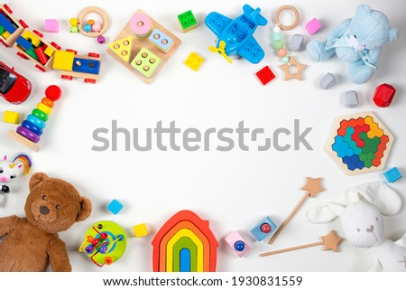 Baby kids toys frame. Set of colorful educational wooden and fluffy toys on white background. Top view, flat lay, copy space for text