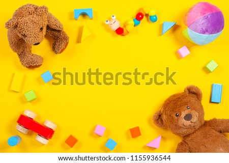 Baby kids toys frame with teddy bear, wooden toy car, colorful bricks on yellow background. Top view #1155936544