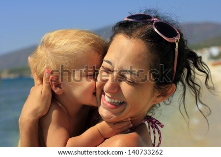 Baby kissing her happy mother