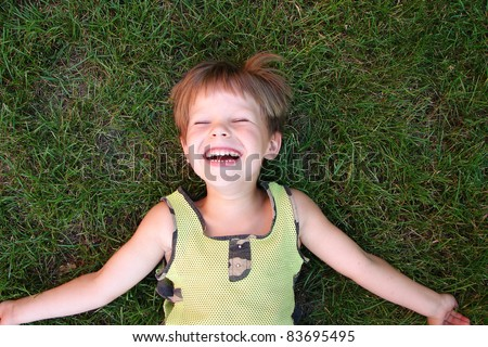 stock photo : Baby laughing, lying on the grass