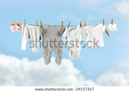 Baby laundry hanging in the sky on a clothesline