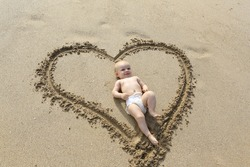 Baby laying down in the heart shape print on the sand. I love my baby.