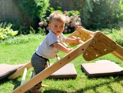 Baby learning to stand and climb on a Pikler triangle