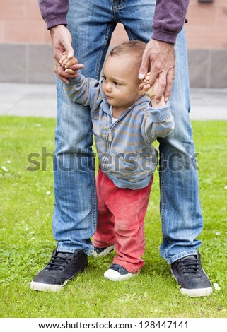 Baby learning to walk and making his first steps holding the hands of his father.