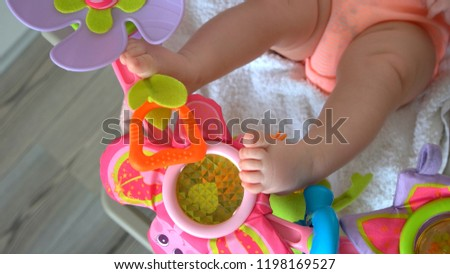 Baby legs and rattle toys. Newborn baby playing with toys in crib. Infants motor development.
