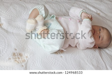 Baby lie one bed with arm and leg held