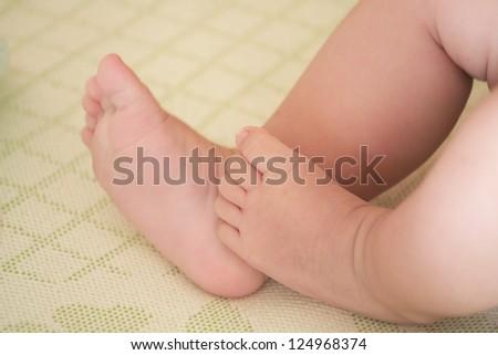Baby little feet touch each other on mat