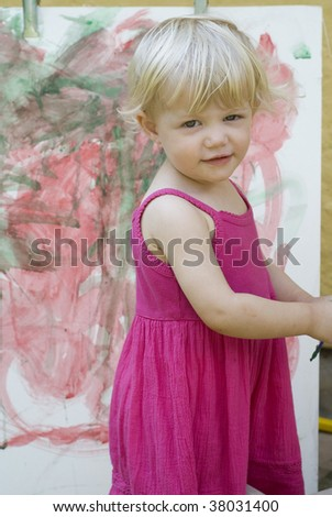 Baby little girl playing with paint artist