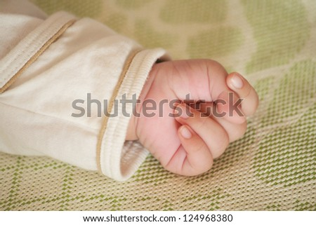 Baby little hand gripping on mat in Summer