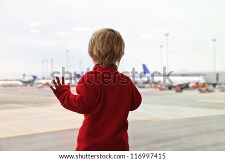 baby looking at planes in the airport