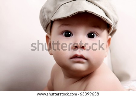 Baby looking at the camera with gray beret - stock photo
