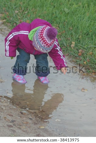 Baby , looking in puddle