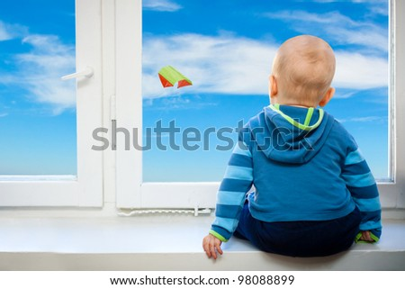 Baby looking out a window  on kite flying in the blue sky