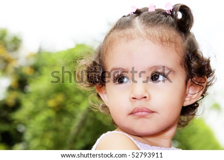 Baby looking up over green background. Outdoor image