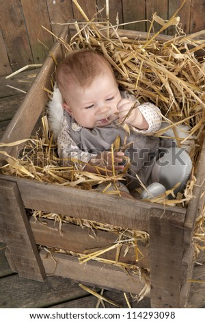Baby lying in a crate with straw
