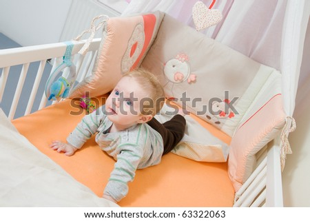 baby lying in the latticed bedsted and plays