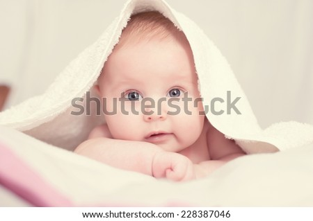 Stock Photo baby lying on a bed under towel
