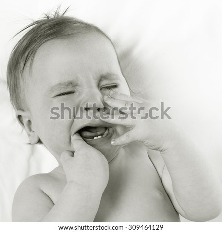 baby lying on a white pillow and crying teething