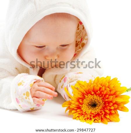Baby lying on floor and looking at orange flower