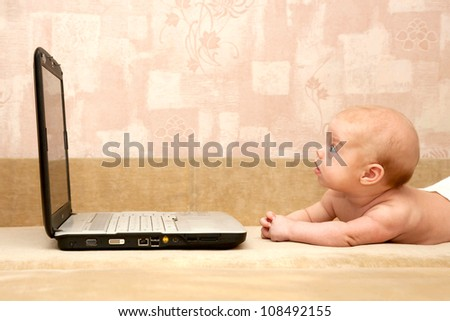 Baby lying on the couch and working on a laptop, carefully looking at the monitor.