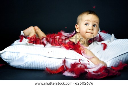 baby lying on the pillow in in white with red fluff