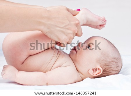 Baby massage. Mother massaging baby's legs. Isolated on white background