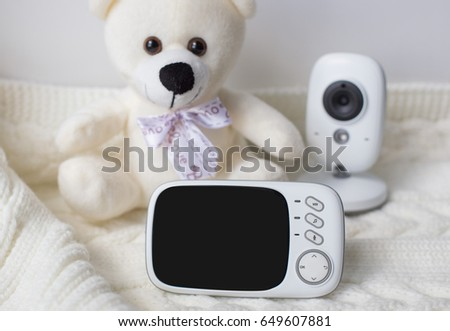 baby monitor for security of the baby surrounded by a teddy bear on a light background. close-up #649607881