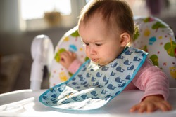 Baby not liking the food and spits it out. Sitting in a high chair in bright living room. 6- 12 months old. Feeding baby concept