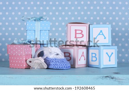 Baby nursery bootie dummy pacifier and baby letters pink and blue gift boxes against a vintage aqua blue table and polka dot background for baby shower or newborn girl greeting card
