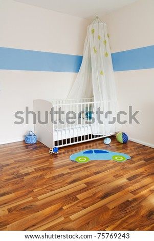 Baby nursery with bed and blue colored stripe on wall