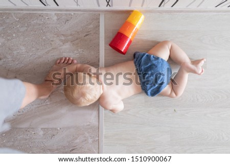 Baby on a floor near mother legs asking for help or forgiveness holding with hand and looking above after play with tower not guilty and innocent in jeans #1510900067