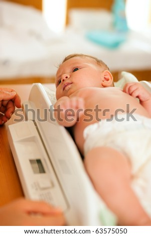 Baby on a weight scale, her mother or a doctor is checking health and development of the newborn
