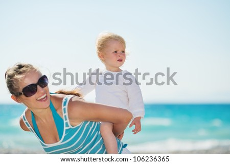 Baby on beach piggybacking mother and looking on copy space