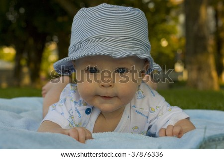 Baby on coverlet  in hat from sun