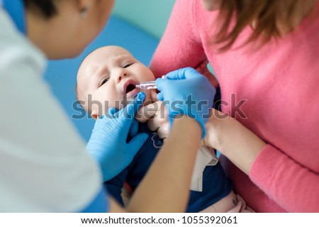 Baby on mothers hand at hospital. Nurse making infant oral vaccination against rotavirus infection. Children health care and disease prevention.
