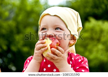 baby on natural green background eating apple - stock photo