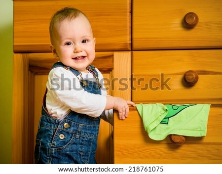 Baby opening drawer with clothes on wooden furniture at home