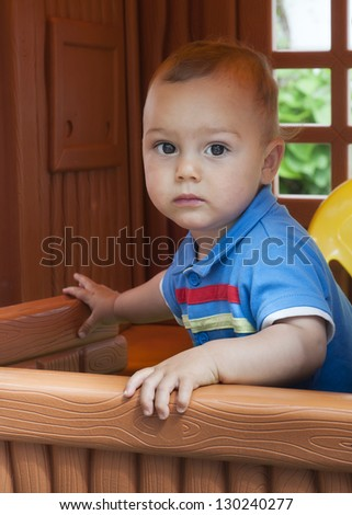 Baby or a toddler child playing in a plastic toy playhouse in an yard or an outdoor playground.