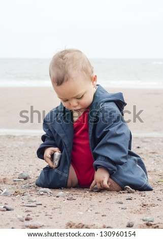 Baby or a toddler child playing with sand and pebbles on a beach on a cold day.