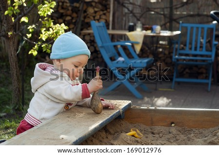 Baby or toddler child playing with sand at sandpit or sandbox in a patio garden.