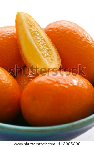 Baby oranges arranged in a blue pottery bowl. Close up.