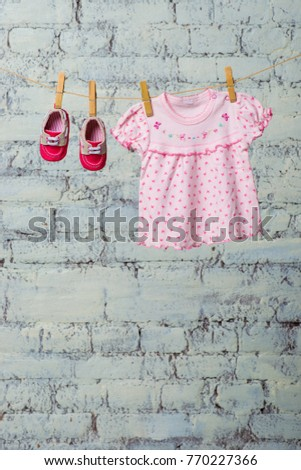 Baby pink dress and red shoes for the girl, dry on a rope against a white brick wall. #770227366