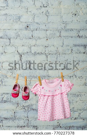 Baby pink dress and red shoes for the girl, dry on a rope against a white brick wall. #770227378