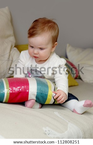 baby play with a pillow.
