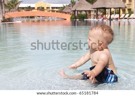 Baby playing and splashing in a tropical resort pool