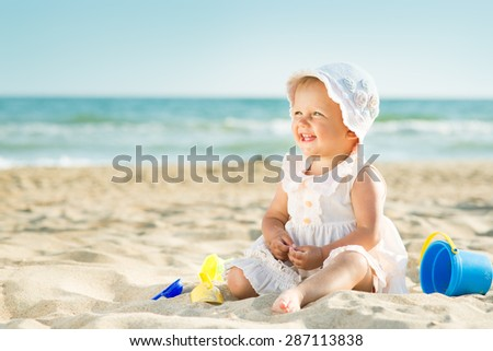 Baby playing on the sandy beach near the sea