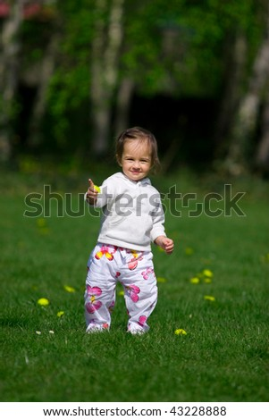 Baby playing on the spring meadow - stock photo
