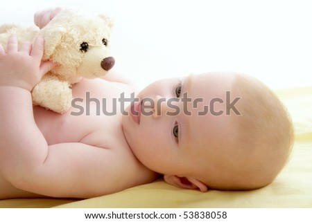 baby playing teddy bear laying on yellow bed