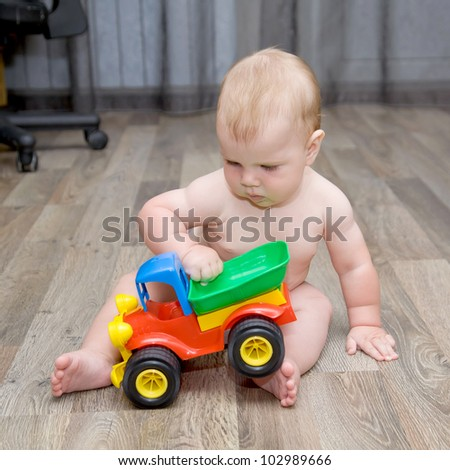 baby playing with a toy car