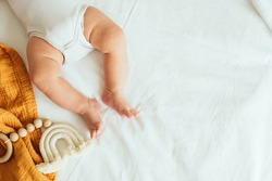 Baby playing with a wooden toy on white linens background. Mockup. Top view. Copy space.